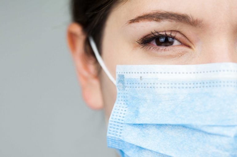 Close up of a doctor in blue uniform wearing blue protective sur